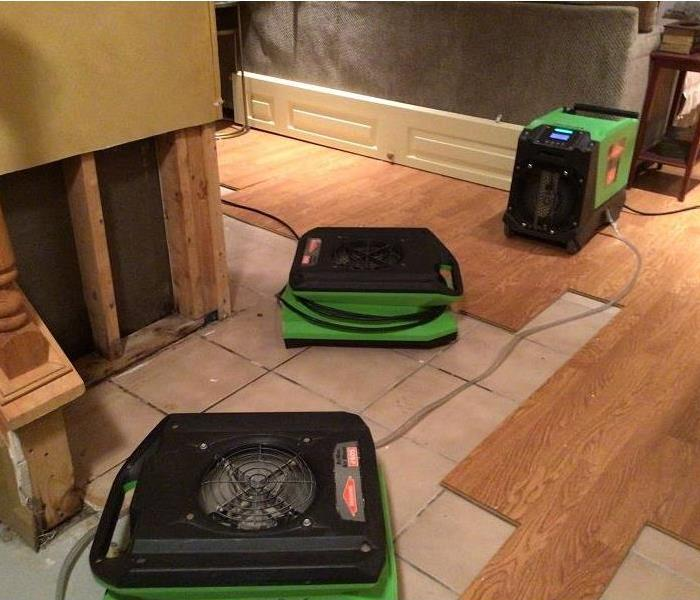 3 SERVPRO green pieces of drying equipment set up near the affected area and on the hardwood floors.