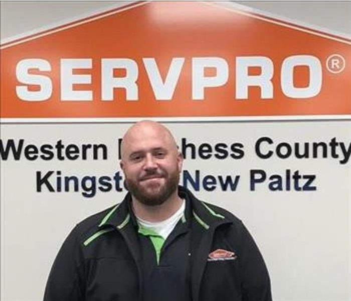 A photo of a smiling employee in a black jacket standing in front of the SERVPRO orange house logo