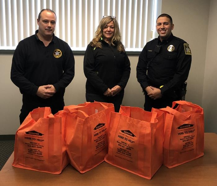 A photo of 3 people surrounded by orange bags of donated food items