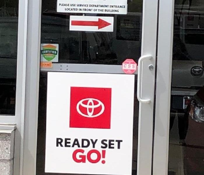 A photo of glass doors of a car dealership displaying the Certified: SERVPRO Cleaned badge
