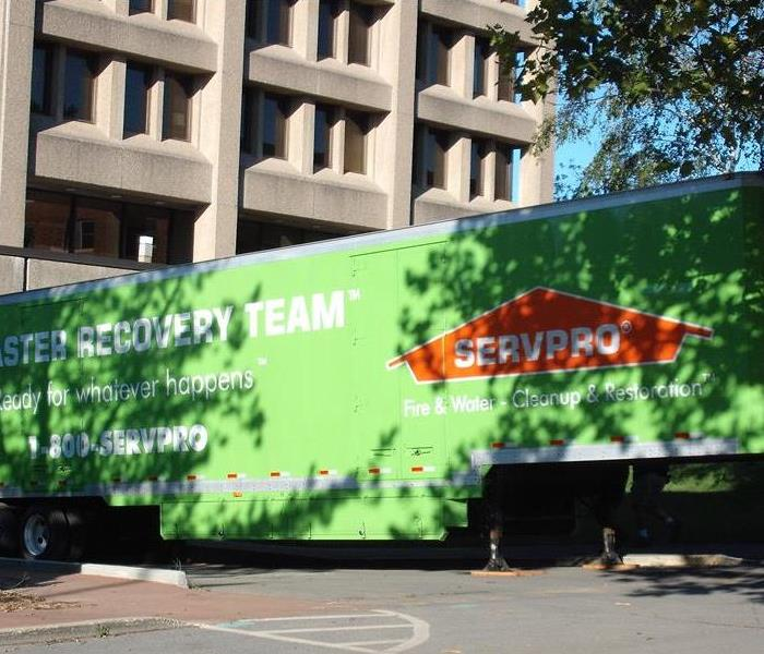 A large SERVPRO semi truck parked at a commercial building