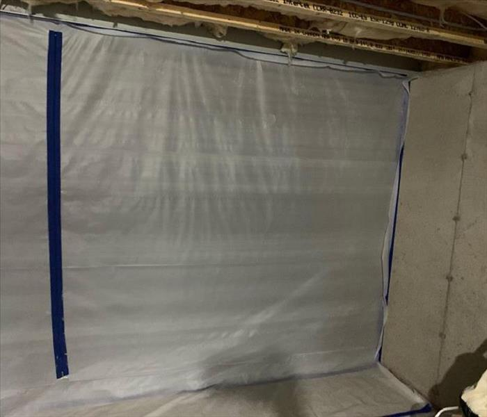A dried out basement with plastic containment sheets up to prevent further damage