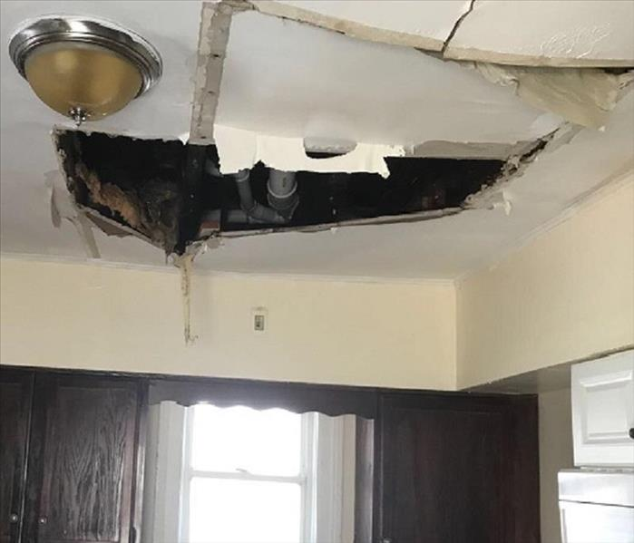 A large tear, split and hole in a kitchen ceiling from water damage in a burst pipe above.