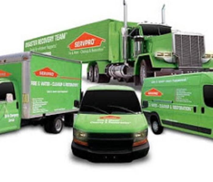 A display of SERVPRO green vans, trucks and tractor trailers
