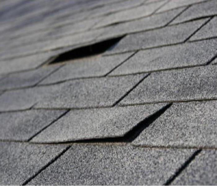 A section of a gray roof of a home with 2 damaged shingles